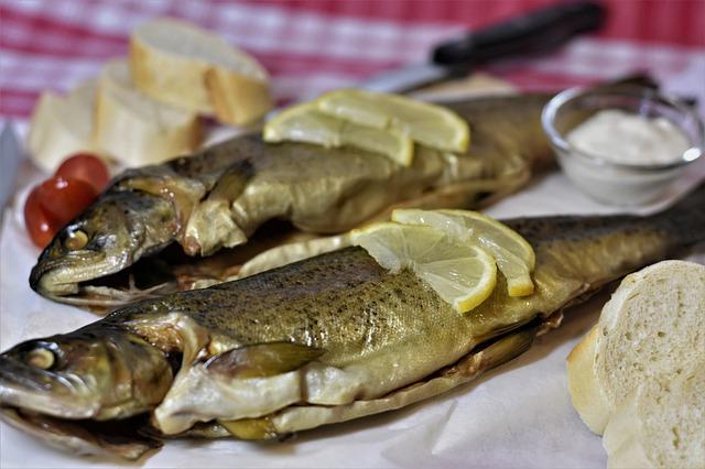 Fertig zubereitete Forellen mit Zitrone und Butter servieren