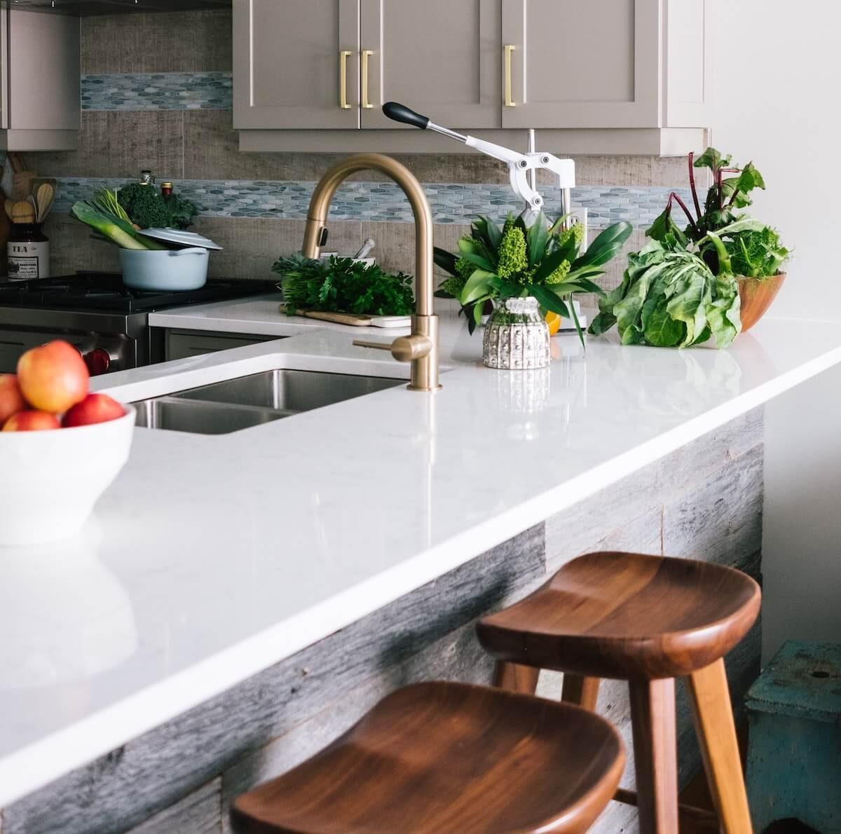Küche mit weißer Arbeitsplatte und Bar bzw Teke mit Barhockern